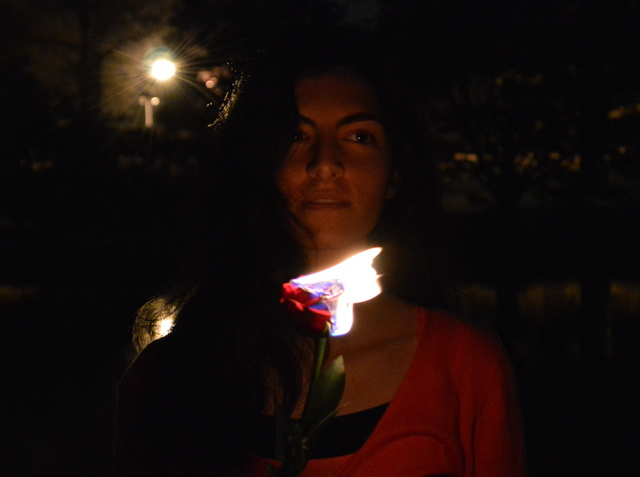 Maryam's face lit by a burning rose while she sits