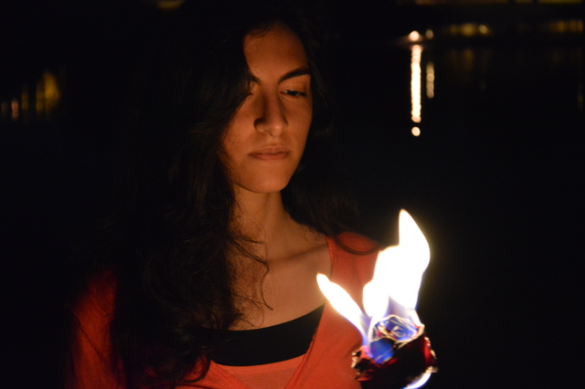 Maryam standing, holding a burning rose